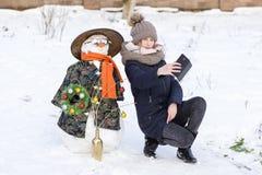 La chica joven feliz está tomando imágenes del selfie con un muñeco de nieve Imagen de archivo libre de regalías