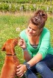 La chica joven feliz palying su perro Foto de archivo libre de regalías