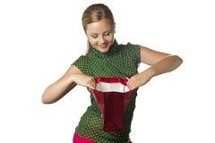 La chica joven feliz sorprendida está abriendo el bolso del regalo Imagen de archivo