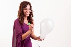 La chica joven feliz va a romper un globo con un dardo Imagenes de archivo