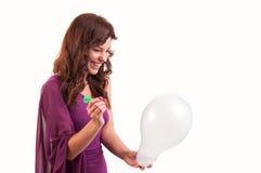 La chica joven feliz va a romper un globo con un dardo Fotografía de archivo libre de regalías