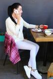 La chica joven habla por el teléfono, sonriendo, sosteniendo la taza y sentándose encendido Foto de archivo