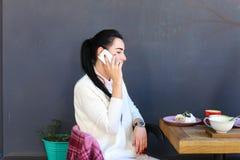 La chica joven habla por el teléfono, sonriendo y sentándose en perfil en el ch Fotos de archivo