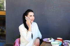 La chica joven habla por el teléfono, sonriendo y sentándose en silla en el tabl Imagen de archivo libre de regalías