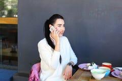 La chica joven habla por el teléfono, sonriendo y sentándose en silla en el tabl Fotografía de archivo libre de regalías