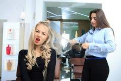 La chica joven hace el peinado en un salón de belleza foto de archivo