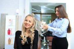 La chica joven hace el peinado en un salón de belleza fotos de archivo