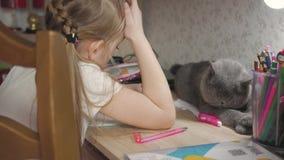 La chica joven hace su preparación en la tabla bajo luz de una lámpara afición creativa de la pequeña princesa forma de vida de almacen de video