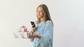 La chica joven hace una foto de presentes festivos en el fondo blanco metrajes