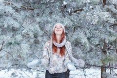 La chica joven hermosa alegre bastante feliz con la diversión del rydimi del pelo en el bosque nevoso y goza de la primera nieve  Fotos de archivo libres de regalías