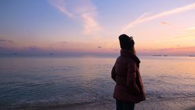 La chica joven hermosa camina a lo largo de la playa a una puesta del sol hermosa en la cámara lenta metrajes
