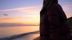 La chica joven hermosa camina a lo largo de la playa a una puesta del sol hermosa en la cámara lenta almacen de metraje de vídeo
