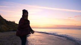 La chica joven hermosa camina a lo largo de la playa a una puesta del sol hermosa en la cámara lenta almacen de video