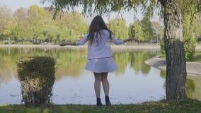 La chica joven hermosa con el pelo largo se vistió en la ropa blanca que hacía girar cerca a un lago en parque en un día del otoñ almacen de metraje de vídeo