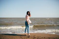 La chica joven hermosa con el pelo negro en una camisa y vaqueros se divierte en la playa del mar de Azov Fotografía de archivo