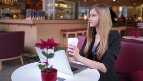 La chica joven hermosa con el pelo rubio en la chaqueta negra se está sentando en el café Ella toma un café y trabaja con metrajes