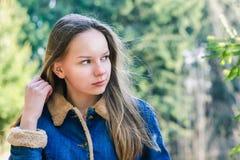 La chica joven hermosa con el pelo rubio oscuro largo en una chaqueta del dril de algodón mira en la distancia en un parque verde fotografía de archivo