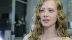 La chica joven hermosa con el pelo rubio rizado largo y los ojos azules se mira antes de maquillaje almacen de video