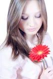 La chica joven hermosa con la flor aisló Imagen de archivo libre de regalías