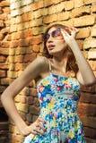 La chica joven hermosa con los labios regordetes atractivos se coloca cerca de la pared en gafas de sol y sonrisas Imágenes de archivo libres de regalías