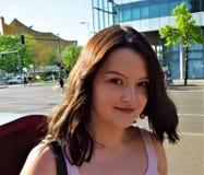 La chica joven hermosa con marrón grande observa en el centro de ciudad Fotos de archivo