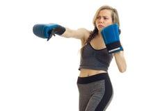 La chica joven hermosa con una guadaña en un traje gris de los deportes hace en guantes de boxeo Fotos de archivo libres de regalías
