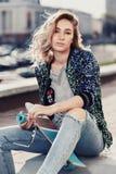 La chica joven hermosa de moda se sienta Fotos de archivo libres de regalías