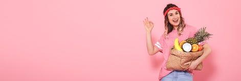 La chica joven hermosa en camiseta rosada, sostiene un bolso lleno de la paja de la fruta en fondo rosado imágenes de archivo libres de regalías
