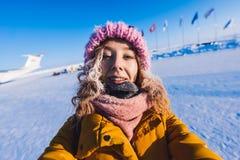 La chica joven hermosa en del amarillo una chaqueta y un rosa abajo hizo punto el casquillo con el pelo rojo en una helada en el  Imagen de archivo libre de regalías