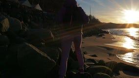 La chica joven hermosa en el fondo de los rayos del ` s del sol está caminando a lo largo de rocas en la costa costa del mar Ropa almacen de video