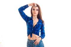 La chica joven hermosa en la camisa azul con el pecho entornado guarda su mano cerca del pelo y la mirada de la cámara foto de archivo