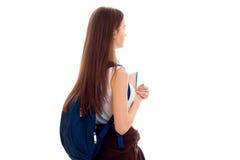 La chica joven hermosa en la camisa blanca y con una cartera dio vuelta el suyo de nuevo a la cámara Foto de archivo