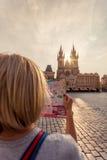 La chica joven hermosa en Praga mira el mapa de la ciudad Imágenes de archivo libres de regalías
