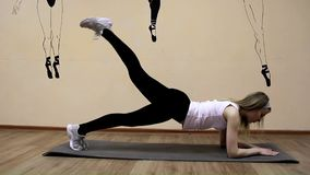 La chica joven hermosa en ropa de deportes hace ejercicios en una mentira de la extensión almacen de metraje de vídeo