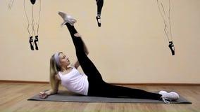 La chica joven hermosa en ropa de deportes hace ejercicios en una mentira de la extensión almacen de video