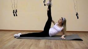 La chica joven hermosa en ropa de deportes hace ejercicios en una mentira de la extensión metrajes