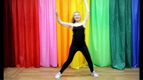 La chica joven hermosa en la ropa de deportes que hace danza simple se mueve