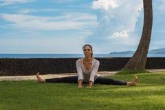 La chica joven hermosa en túnica hace la práctica de la yoga, meditación, estirando asana en una playa del océano en la isla Indo fotografía de archivo libre de regalías