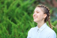 La chica joven hermosa en un parque en un fondo del abeto ramifica Fotografía de archivo