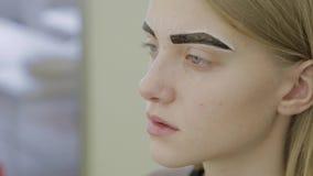 La chica joven hermosa en un salón de belleza está esperando la pintura de la ceja que se absorberá metrajes