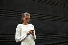 La chica joven hermosa en un suéter ligero que coloca el fondo cercano de la promoción para su hace publicidad Fotos de archivo libres de regalías