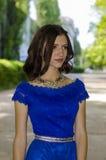 La chica joven hermosa en un vestido azul está mirando al lado Fotos de archivo