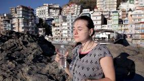 La chica joven hermosa es música que escucha con los auriculares en la playa almacen de video