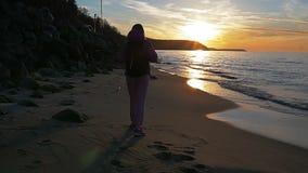 La chica joven hermosa está caminando a lo largo de la playa en el fondo de los rayos del sol Ropa rosada, tiempo de primavera, c almacen de video