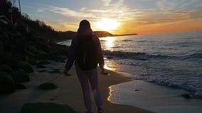 La chica joven hermosa está caminando a lo largo de la playa en el fondo de los rayos del sol Ropa rosada, tiempo de primavera, c metrajes