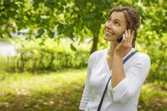 La chica joven hermosa está llamando por el teléfono en parque verde del verano Imagen de archivo