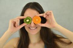 La chica joven hermosa está sosteniendo la fruta de kiwi y la mandarina Imagen de archivo