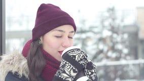 La chica joven hermosa exhala el aire frío, sonrisas y el café de las bebidas de una taza en un parque del invierno almacen de metraje de vídeo