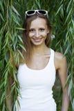 La chica joven hermosa feliz está en las hojas del verde, vidrios, día de verano al aire libre, las miradas sonrientes Imagen de archivo libre de regalías