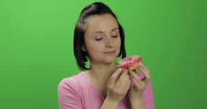 La chica joven hermosa feliz que presenta y quiere comer un buñuelo Llave de la croma metrajes